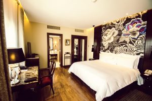 hotel room at Country Club Lima with wood flooring, king size bed, writing desk, marble bathroom