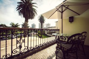 Room balcony with view of palm trees, golf green, and San Isidro office towers