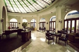 Los Vitrales lobby bar with skylight ceiling, piano, and comfortable seating