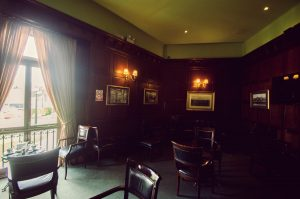 English Bar at Country Club Lima features dim lighting, historic photographs, and dark wood furnishings