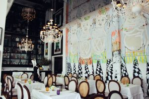 Dining room at Tragaluz Restaurant with chandeliers and art painted onto the walls