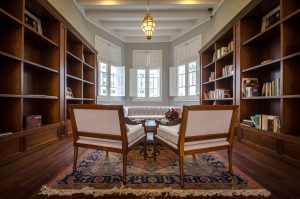 Two chairs on rug with bookshelves on each side