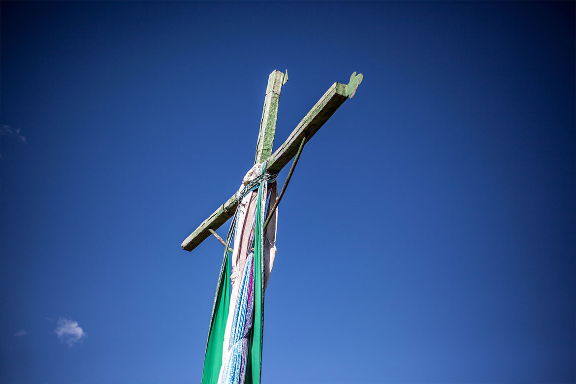 A cross decorated with colored ribbons stand out against a deep blue sky in Cusco