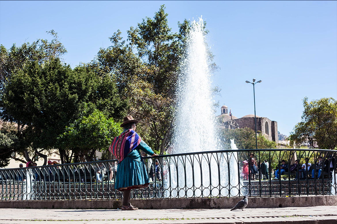 Woman in tradition Andean skirt and hat with a small bundle tied to her back looks at a fountain in the historic center of Cusco