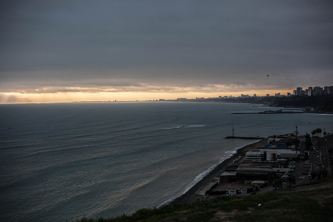 Cloud cover lifts to reveal sun set on Lima coast