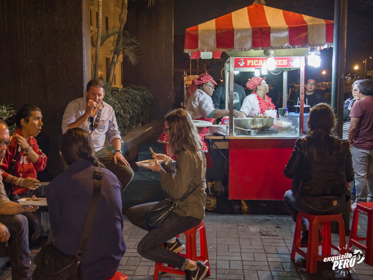 Tourists sitting down eating in Lima with a street vendor in the background at night