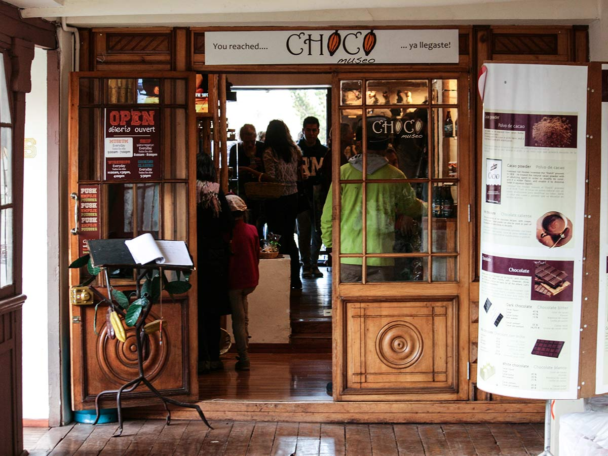 Wood door entrance of ChocoMuseo in Cusco with people inside.