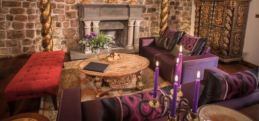 A sitting area with intricate woodwork furniture and a fireplace at Aranwa Cusco Boutique Hotel.