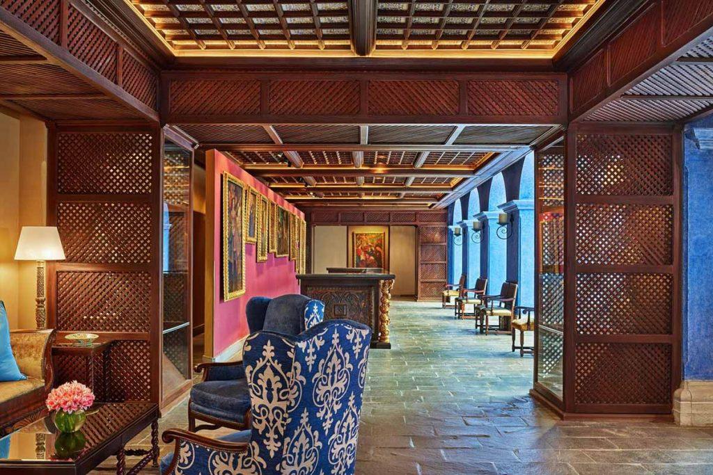 A long hall with pieces of colonial artwork at Palacio del Inka Cusco.
