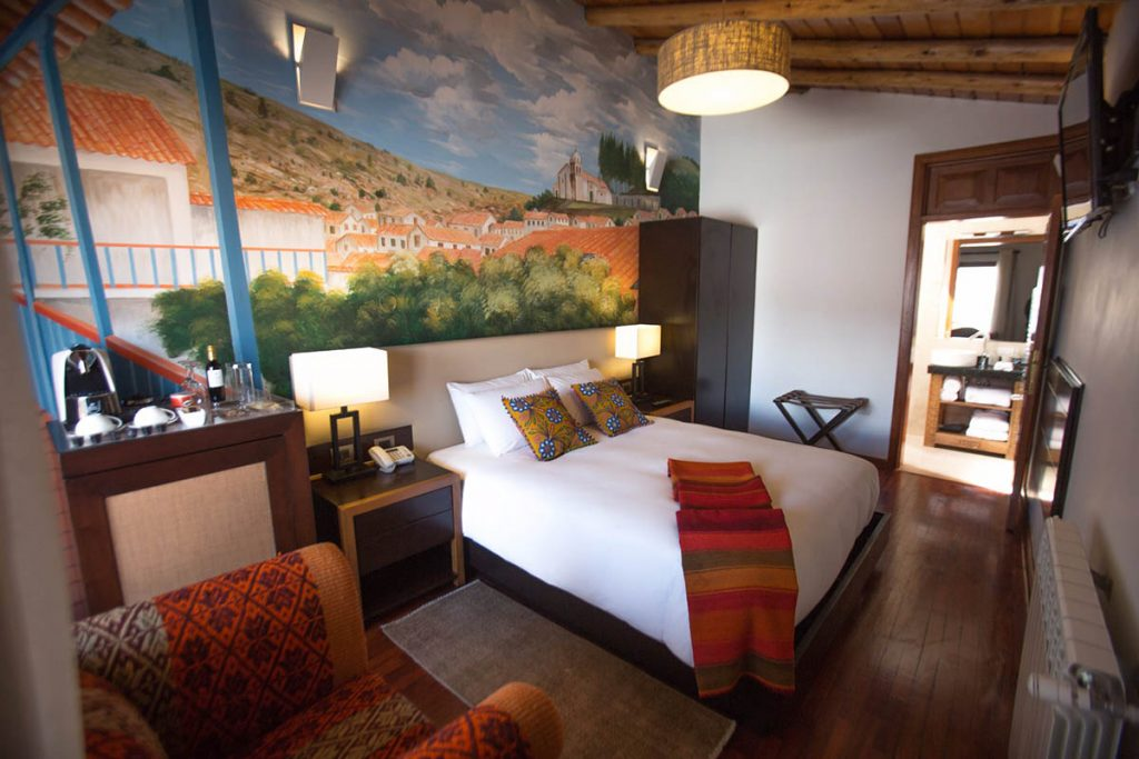 Tocuyeros Boutique Hotel's Queen Suite with a mural of Cusco's hilly skyline.