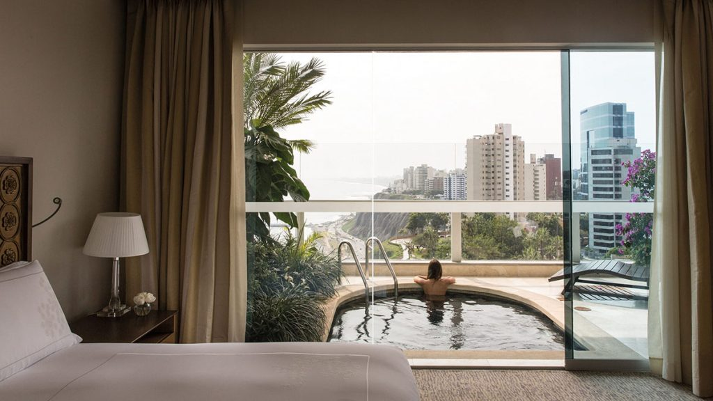 A woman soaks in her honeymoon suite's private pool looking out over the coast of Lima in Belmond Miraflores Park.