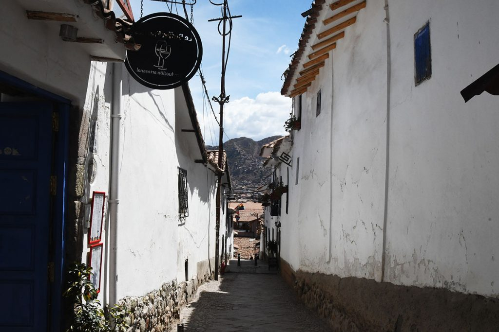 A romantic, narrow cobblestoned street with white-walled buildings in Cusco's San Blas neighborhood.