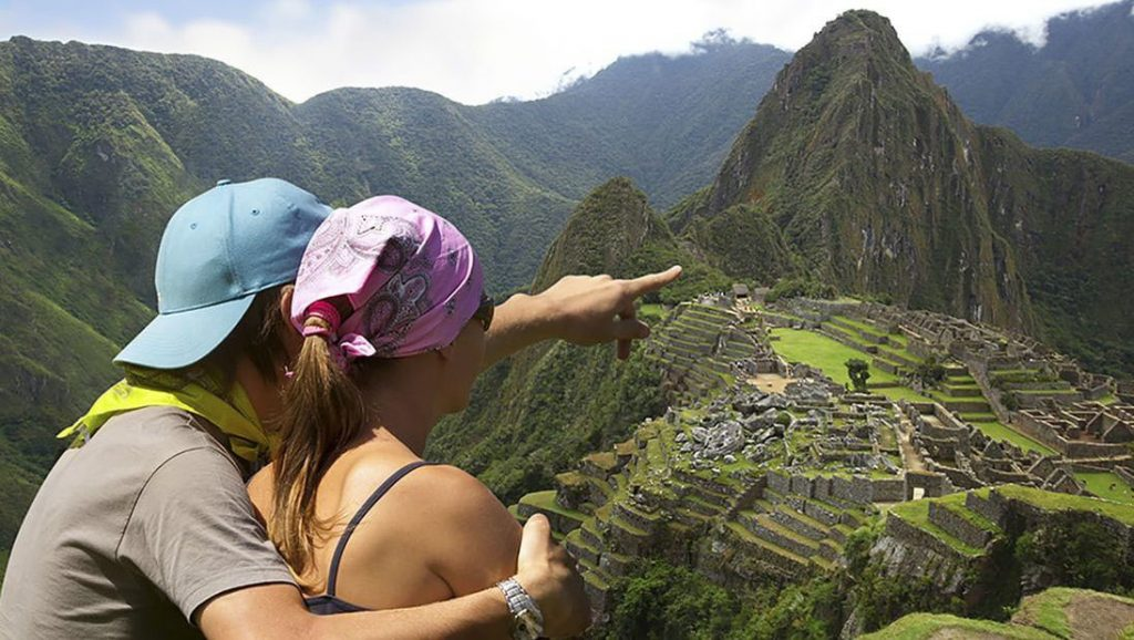 Couple point to the Machu Picchu ruins from lookout point with Huayna Picchu peak in the background.