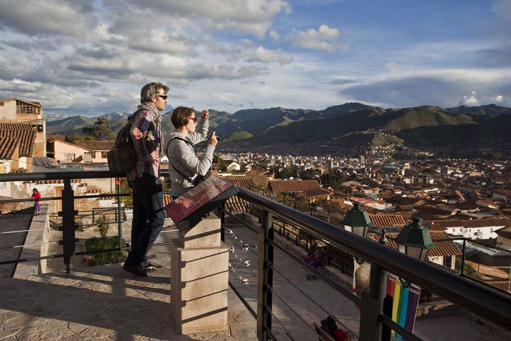 A honeymooning couple looks over the city of Cusco with green mountain in the background.