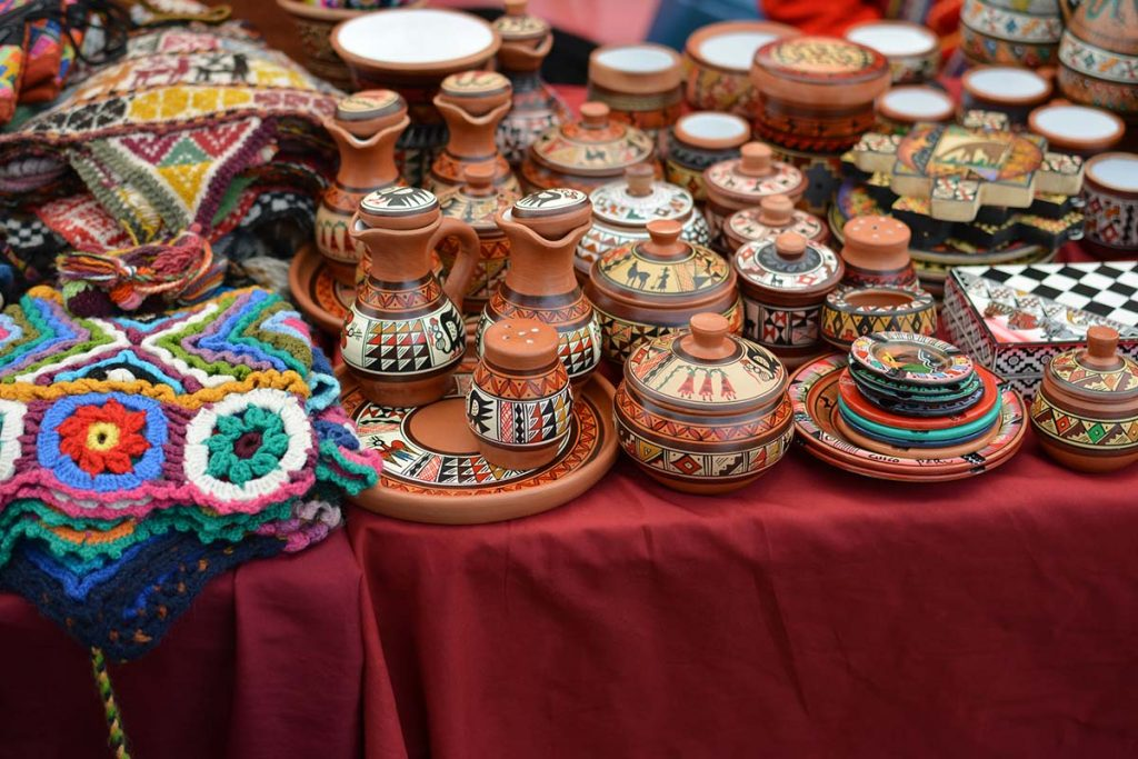 Alpaca wool hats and painted clay bowls and other Peruvian handicrafts at a Cusco market.