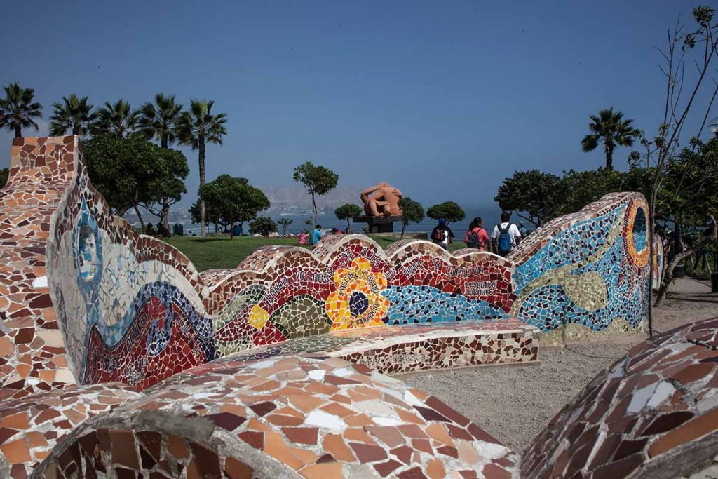 """The colorful mosaic tiled walls at  Parque del Amor (""""Love Park"""") with the famous Victor Delfín statue, El Beso (""""The Kiss""""), and Pacific Ocean in the background."""