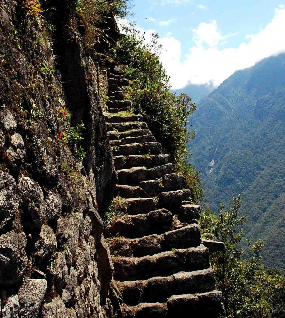 Very steep and uneven steps lead toward the top of Huayna Picchu. To the right is a sharp drop-off into the abyss.