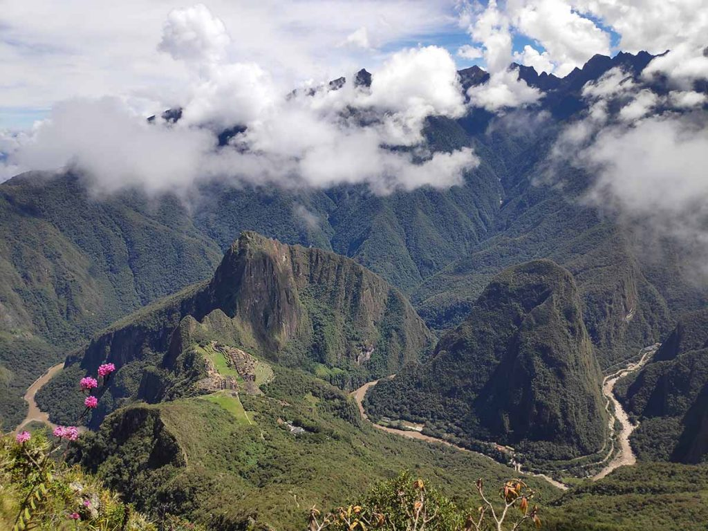 A panoramic view from the top of Machu Picchu Mountain of the Machu Picchu ruins, Huayna Picchu, Andes mountains, and Utcubamba River on a sunny day.