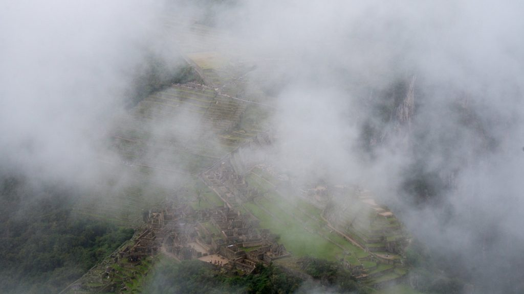 A close up of Machu Picchu taken from the top of Huayna Picchu on a misty day. The clouds mostly cover the ruins.