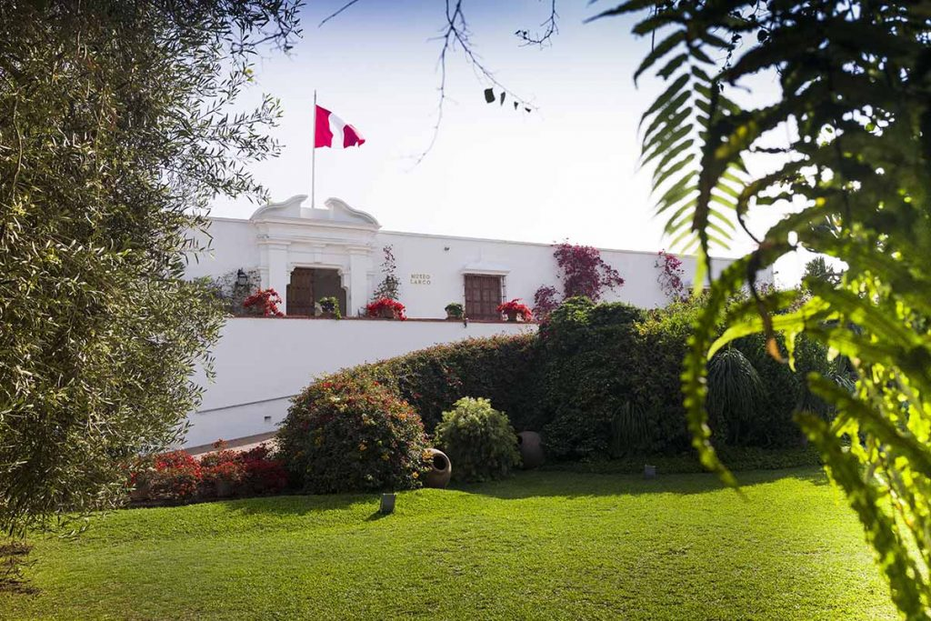 The white painted front facade of Museo Larco and the museum's lush gardens. A Peruvian flag is flown on top of the museum.