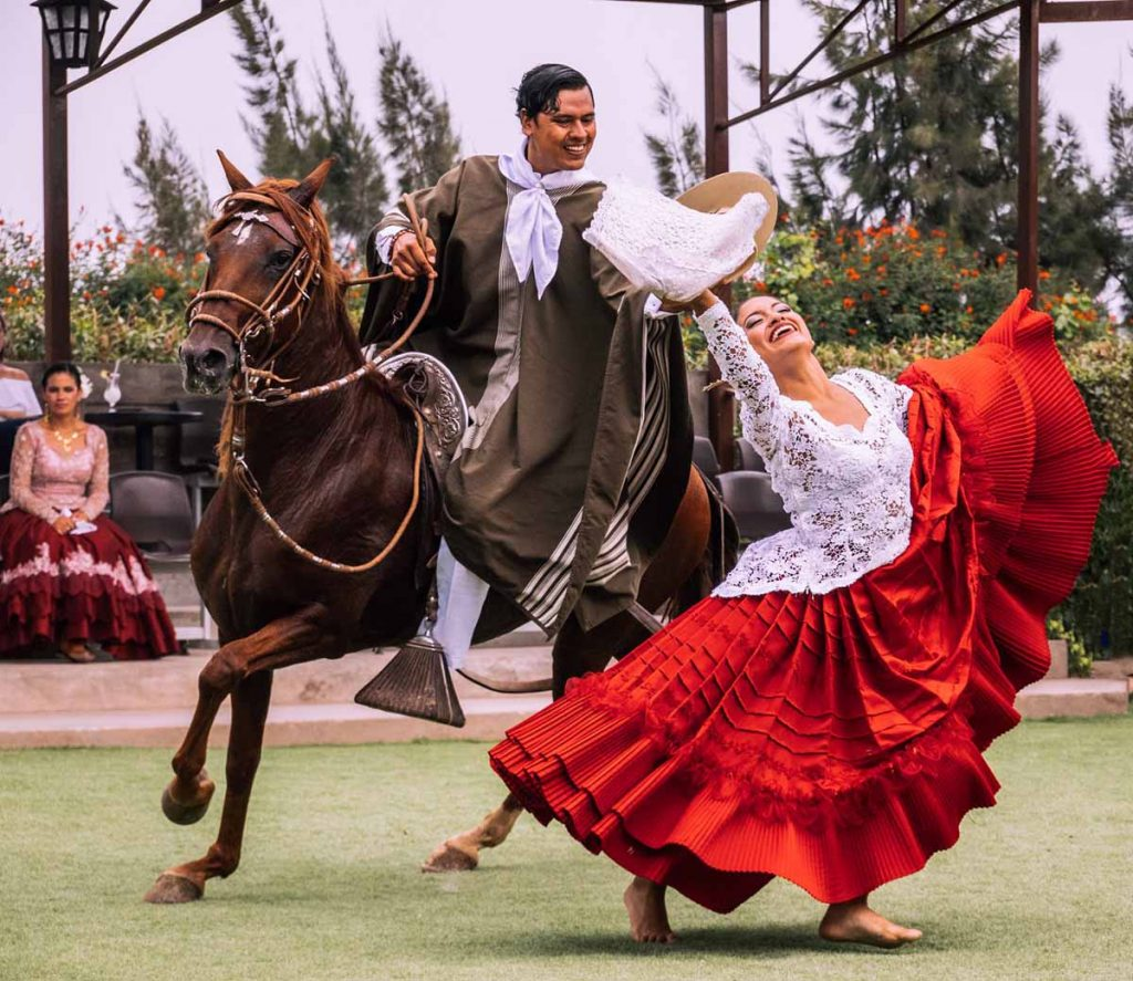 A female dancer in typical dress dancers barefoot in front of a Peruvian Paso Horse and male rider.