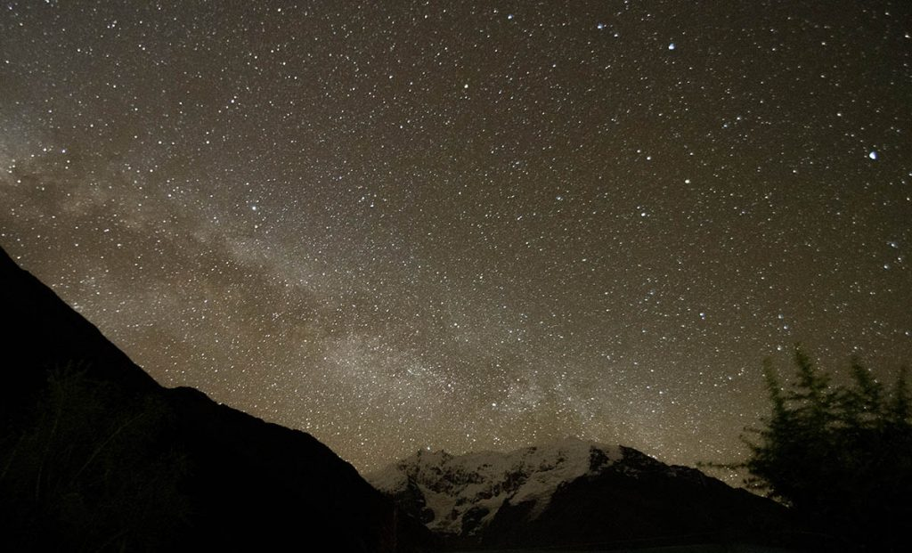 The Milky Way is visible among millions of stars at night over the Andean mountains of the Sacred Valley.
