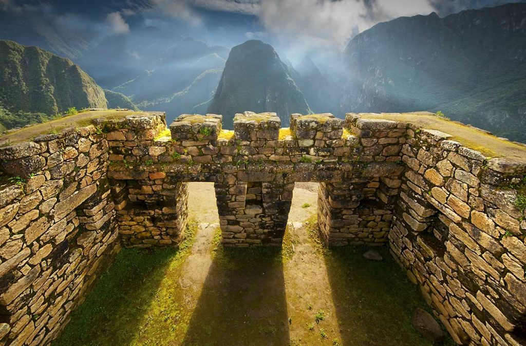 Afternoon sunlight shines through Inca windows at Machu Picchu with green mountains in the background.