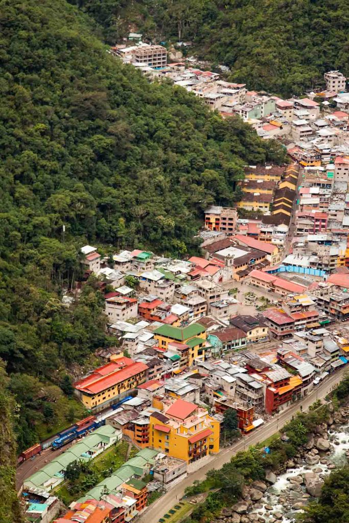 The view from Putucusi Mountain looking down on the town of Aguas Calientes. The houses and buildings are painted bright colors and the river is visible.