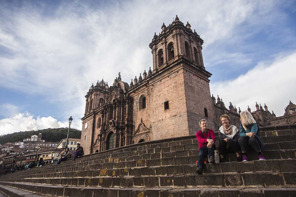 Three tourists sit on the steps leading up to the facade of Cusco Cathedral in the Plaza de Armas.