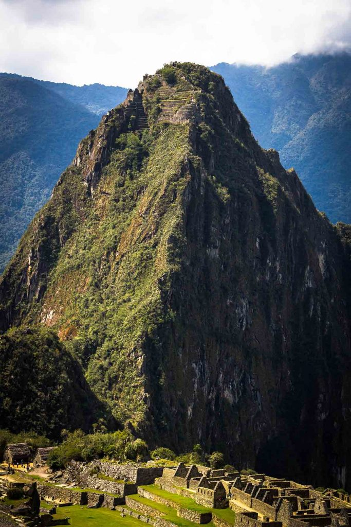 A view of the famous Huayna Picchu Mountain and the ruins atop it. The main ruins of Machu Picchu are also visible in the lower half of the photo.