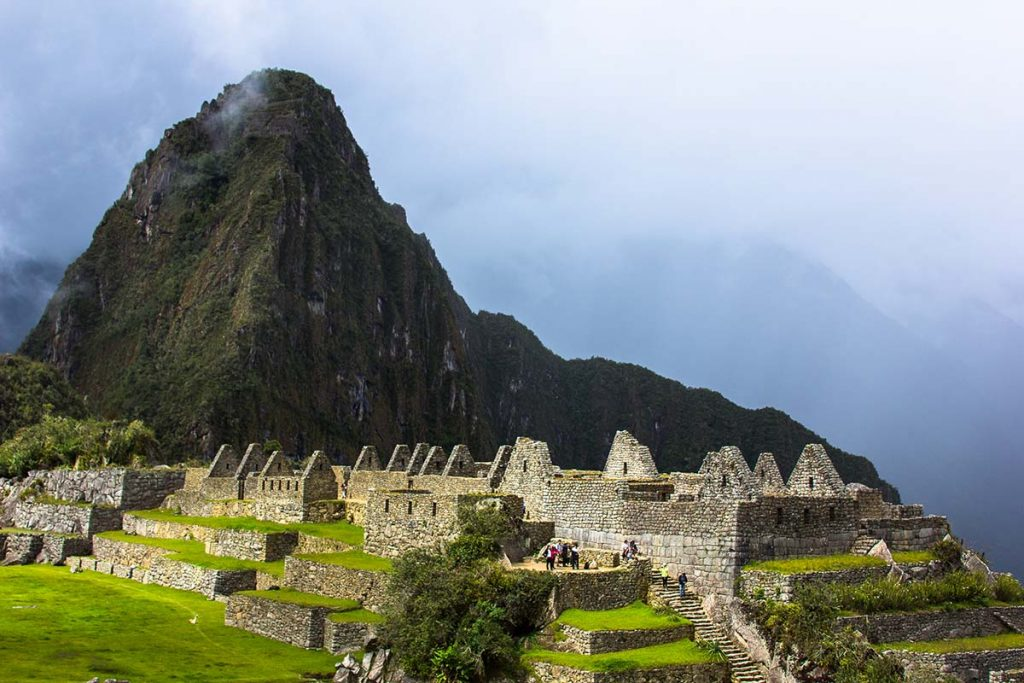 A view of Huayna Picchu on a rainy day. The main ruins of Machu Picchu are visible in the foreground lit up by some sunlight while the mountain is in shadow.