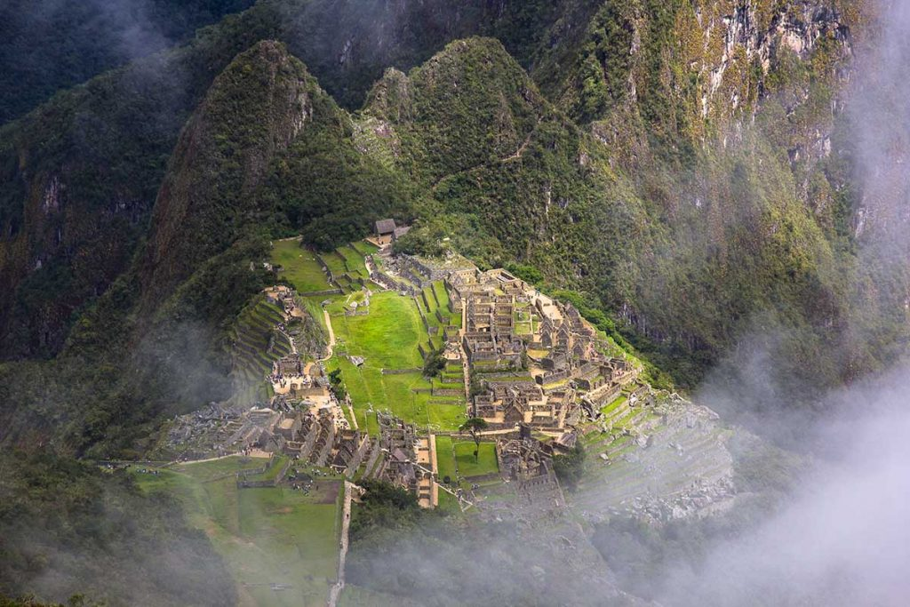 A foggy view of the main ruins visible from Machu Picchu Mountain summit. The ruins are lit up by a small few rays of sunlight.
