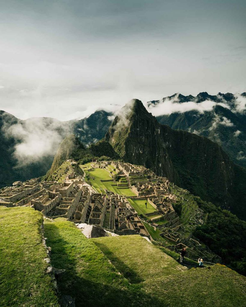 A dark and moody view of the Machu Picchu ruins on a cloudy day. The Inca terraces are covered in bright green grass and the Hauyna Picchu Mountain looms in the background.