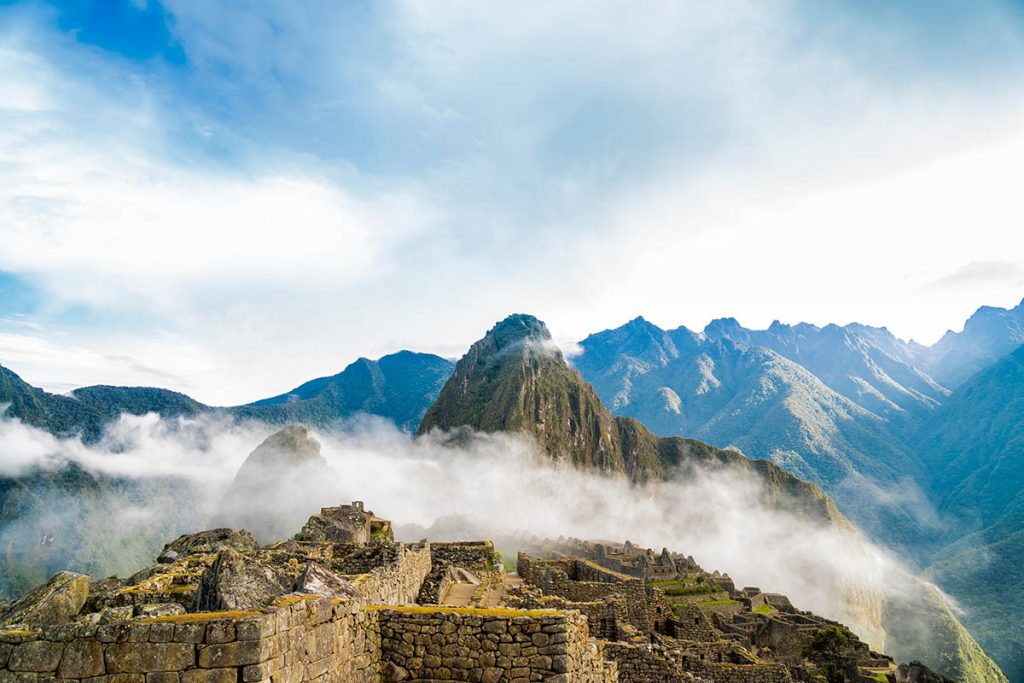 A scene of Machu Picchu and the blue sky with sun beams shining down on the ruins. A low hanging bit of fog rests in the ruins.