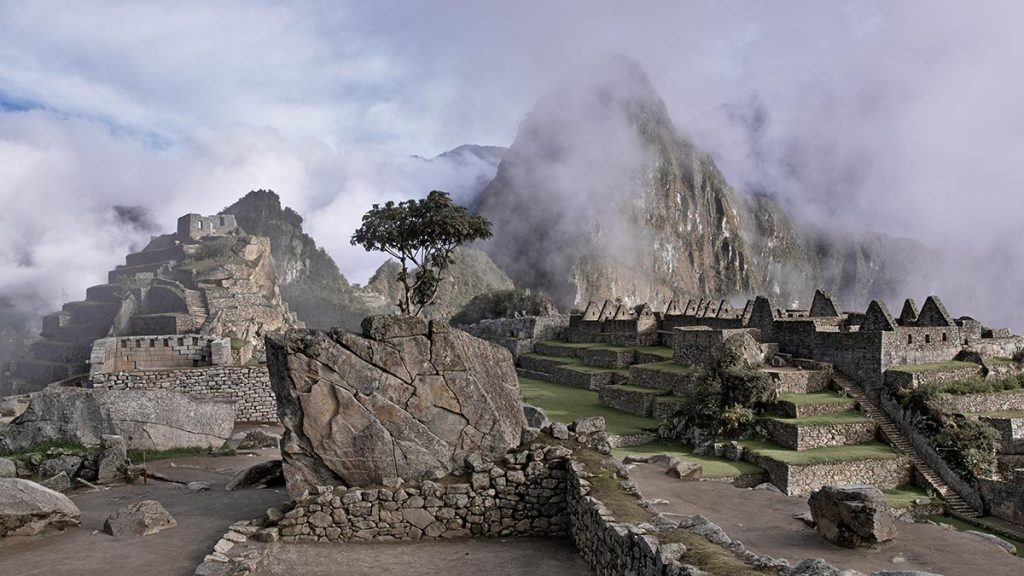 Fog and mist surround the ruins in Machu Picchu on a cloudy day. The ruins stand tall and grey.