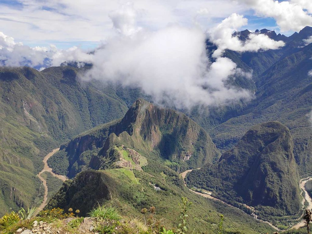 The view looking out from Machu Picchu mountain summit on a partly cloudy day. The main ruins look small in the distance and the Urubamba river is winding below.