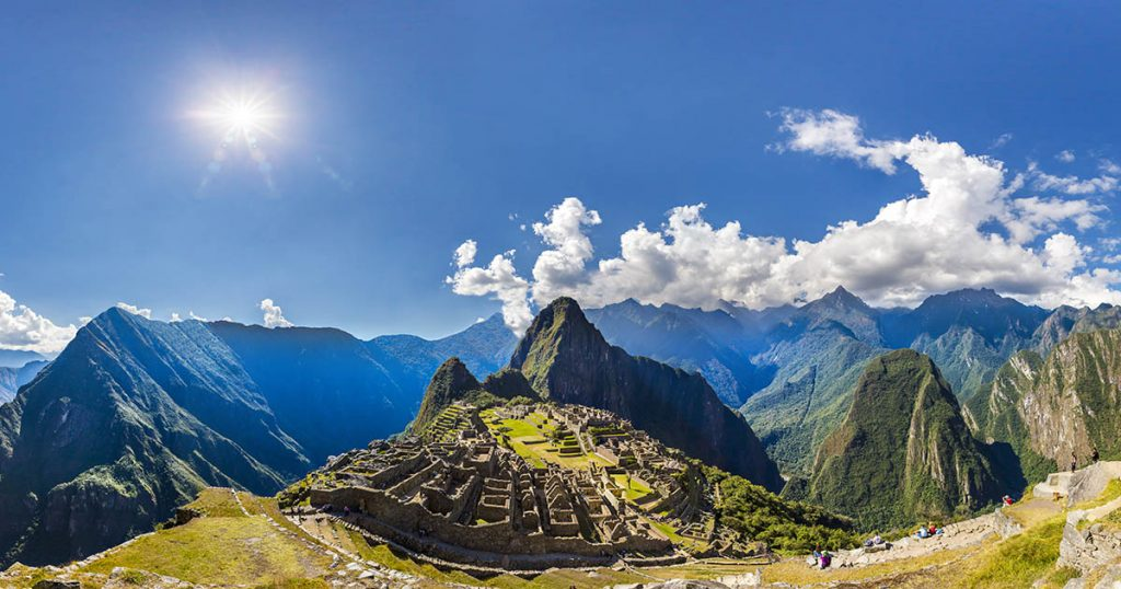 A super-wide angle panoramic view of Machu Picchu. It shows the bright blue sky and shining sun. The ruins and surrounding mountains are lit up.