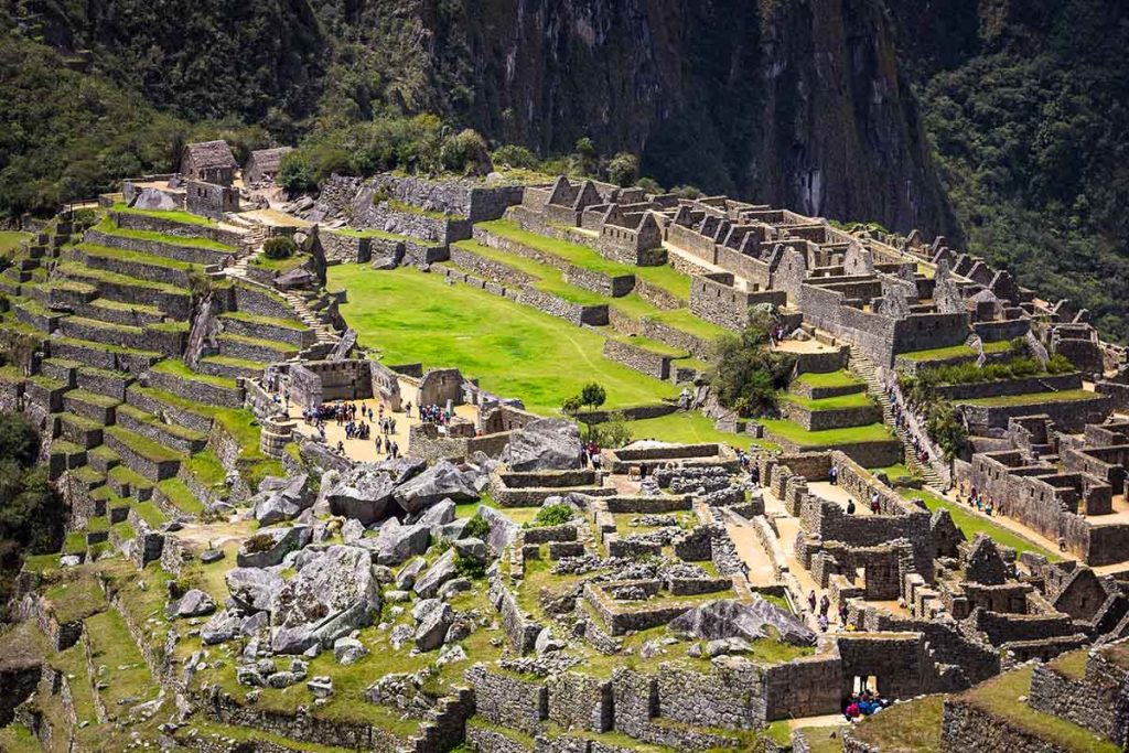 The ruins of Machu Picchu on a bright sunny day. The Inca terraces and Sun Temple are in view.