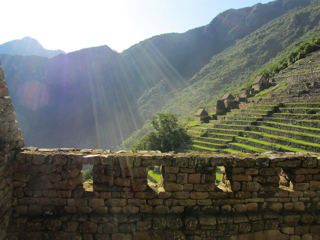 A bright beam of sunlight shines down on the main ruins of Machu Picchu. The Inca terraces are visible in the background.