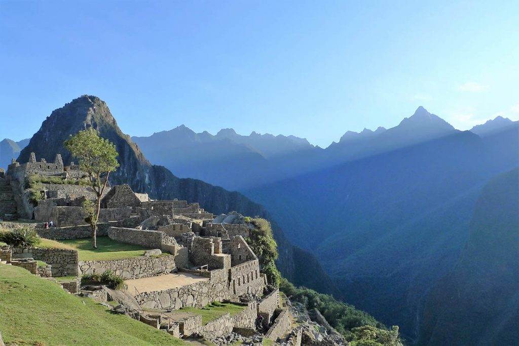 The sun shines on the ruins in Machu Picchu. The sky is a bright blue and the mountains are in shadow.
