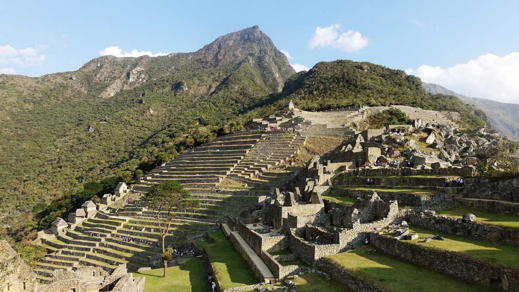 The Inca terraces in Machu Picchu lit up by the afternoon light. Machu Picchu Mountain is visible in the background.
