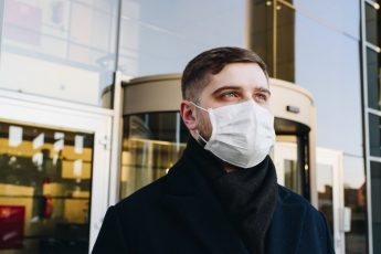 Man with facemask outside building of glass during the Coronavirus COVID-19 pandemic.