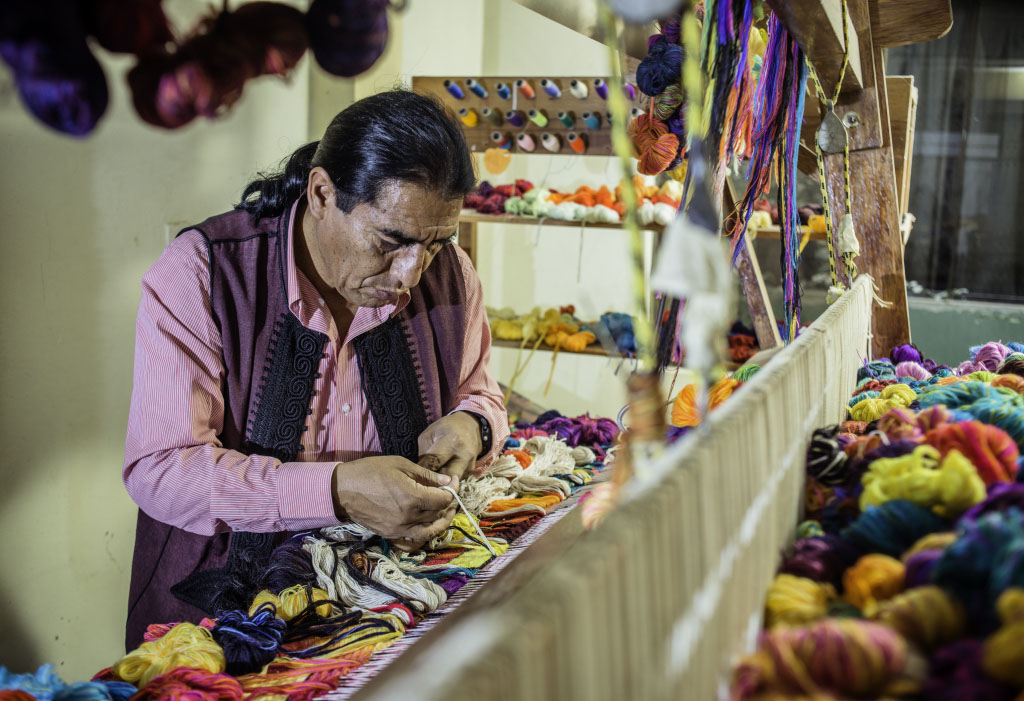 Maximo Laura, wearing a pink shirt and fuchsia vest, in the process of weaving a colorful Peruvian tapestry.