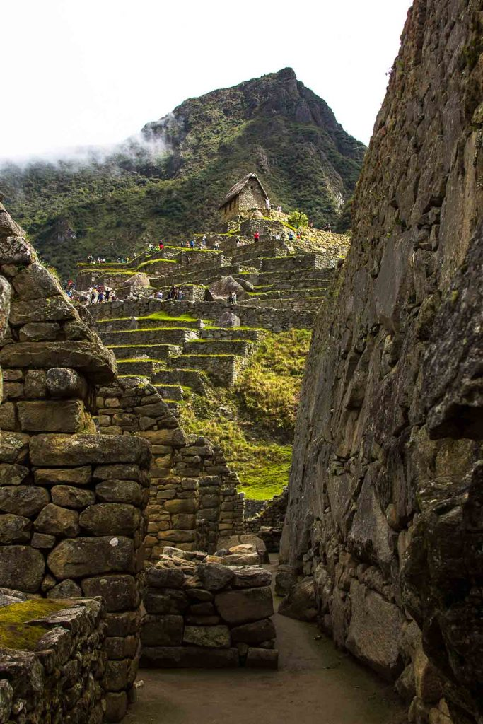 A vertical photograph of the ruins leading up the Guardhouse in Machu Picchu. The Guardhouse is surrounded by tourists and the mountain above has low cloud cover.