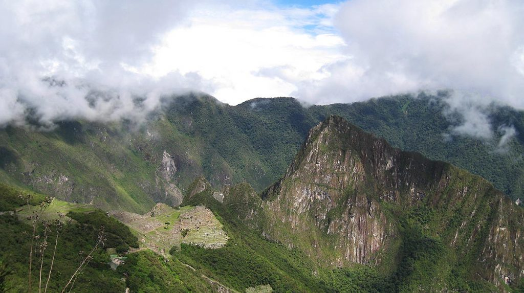 A panoramic view of the ruins and Huayna Picchu from the Sun Gate. The sky is partly cloudy.