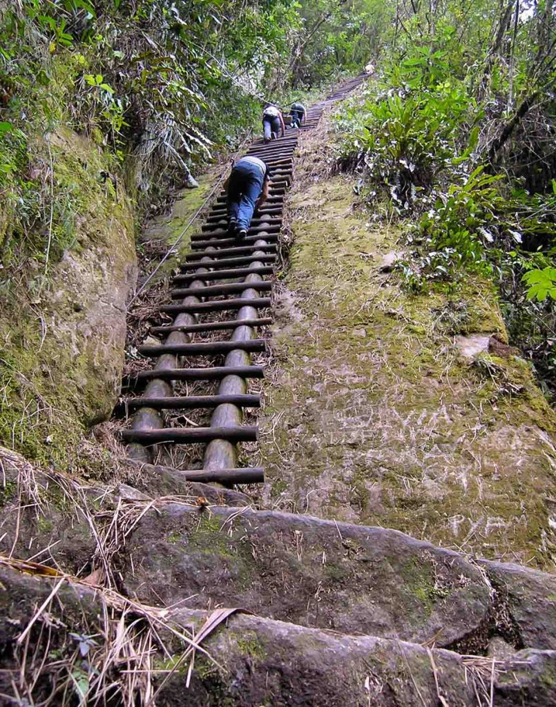 People climb the near vertical ladders leading up the summit of Putucusi Mountain. The ladders are built into the mountain.
