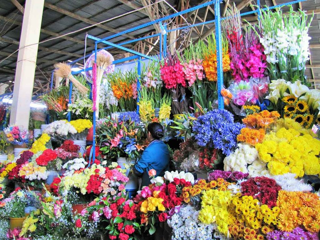 A florist in a blue shirt stands in the middle of a wide variety of colorful flowers at the San Pedro Market in Cusco.