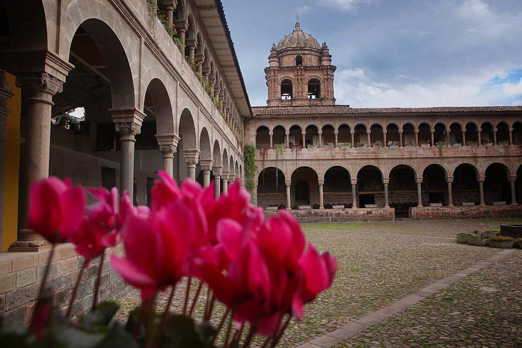 Bright pink flowers are blurred in front of the colonial courtyard of the Santo Domingo Convent with its Renaissance arches.