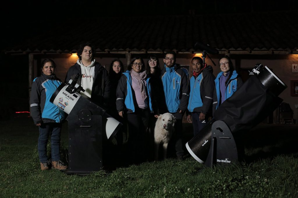 The staff of the Cusco Planetarium stand in a line in matching blue and gray jackets with two large telescopes with the fluffy white family dog in the middle.