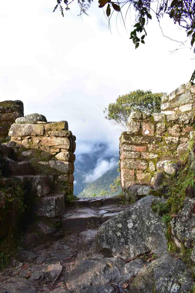 The Sun Gate entrance to Machu Picchu illuminated by the sun. The ruins are surrounded by a rocky path.